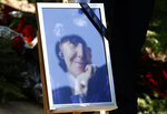 A reflection of a man in the picture of Mirjana Markovic, the widow of former strongman Slobodan Milosevic during her funeral at the yard of his estate in his home town of Pozarevac, Serbia, Saturday, April 20, 2019. Markovic died last week in Russia where she had been granted asylum. The ex-Serbian first lady had fled there in 2003 after Milosevic was ousted from power in a popular revolt and handed over to the tribunal in The Hague, Netherlands. (AP Photo/Darko Vojinovic)