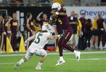 Arizona State quarterback Jayden Daniels, right, eludes the reach of Sacramento State linebacker Marcus Hawkins during the first half of an NCAA college football game Friday, Sept. 6, 2019, in Tempe, Ariz. (AP Photo/Matt York)