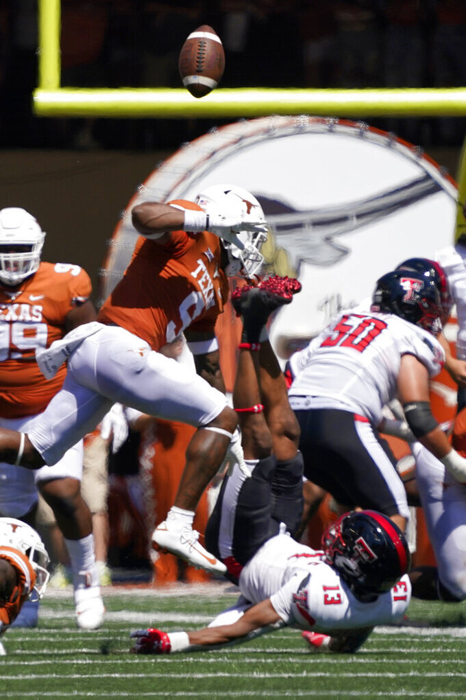 Texas Tech wide receiver Erik Ezukanma (13) loses the ball after being hit by Texas defensive back Josh Thompson (9) during the second half of an NCAA college football game on Saturday, Sept. 25, 2021, in Austin, Texas. Texas intercepted the pass and returned it for a touchdown. (AP Photo/Chuck Burton)