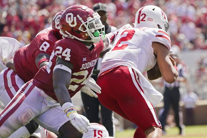 Oklahoma linebacker Brian Asamoah (24) reaches for Nebraska quarterback Adrian Martinez (2) in the second half of an NCAA college football game, Saturday, Sept. 18, 2021, in Norman, Okla. (AP Photo/Sue Ogrocki)
