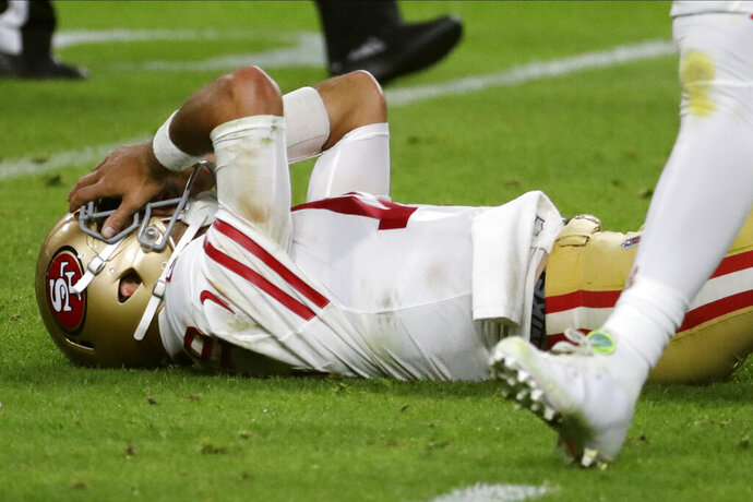 San Francisco 49ers quarterback Jimmy Garoppolo lays on the ground after being hit during the second half of the NFL Super Bowl 54 football game against the Kansas City Chiefs Sunday, Feb. 2, 2020, in Miami Gardens, Fla. (AP Photo/Matt York)