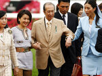 FILE - In this April 29, 2007, file photo, Macao tycoon and owner of Hong Kong horse Viva Pataca Stanley Ho, center, gets a little help from his wife Angela Leung, second left, and an attendant during awarding ceremony at the Sha Tin racecourse in Hong Kong. On Tuesday, May 26, 2020, the family of Stanley Ho, the Macao casino tycoon considered the father of modern gambling in China, has died at 98. (AP Photo/Vincent Yu, File)