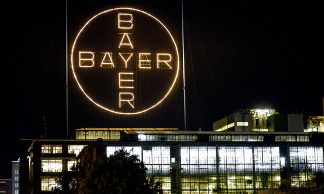 FILE - In this Aug. 9, 2019, file photo, the Bayer logo shines at night at the main chemical plant of German Bayer AG in Leverkusen, Germany. The German pharmaceutical company announced Wednesday, June 24, 2020, it's paying up to $10.9 billion to settle a lawsuit over subsidiary Monsanto's weedkiller Roundup, which has faced numerous lawsuits over claims it causes cancer.  (AP Photo/Martin Meissner, File)