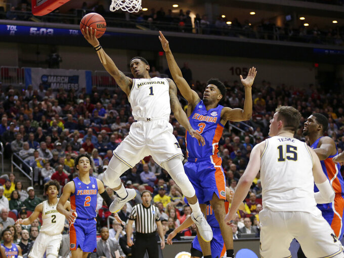 Michigan's Charles Matthews (1) goes to the basket past Florida's Jalen Hudson (3) during the first half of a second round men's college basketball game in the NCAA Tournament, in Des Moines, Iowa, Saturday, March 23, 2019. (AP Photo/Nati Harnik)