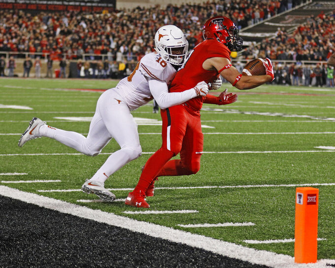 Texas Tech's Mason Reed (29) is tackled by Texas' Davante Davis (18) during the first half of an NCAA college football game Saturday, Nov. 10, 2018, in Lubbock, Texas. (AP Photo/Brad Tollefson)