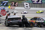 Reed Sorenson (77) and Tyler Reddick, right, pit during a NASCAR Cup Series auto race at Kansas Speedway in Kansas City, Kan., Sunday, Oct. 18, 2020. (AP Photo/Orlin Wagner)