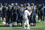 Seattle Seahawks Pete Carroll claps as players, including offensive tackle Brandon Shell (72) huddle during warmups before an NFL football mock game, Wednesday, Aug. 26, 2020, in Seattle. (AP Photo/Ted S. Warren)