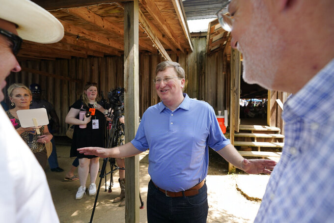 Republican Gov. Tate Reeves laughs as he greets fairgoers at the Neshoba County Fair following his speech before them in Philadelphia, Miss., Thursday, July 29, 2021. The fair, also known as Mississippi's Giant House Party, is an annual event of agricultural, political, and social entertainment at what might be the country's largest campground fair. (AP Photo/Rogelio V. Solis)