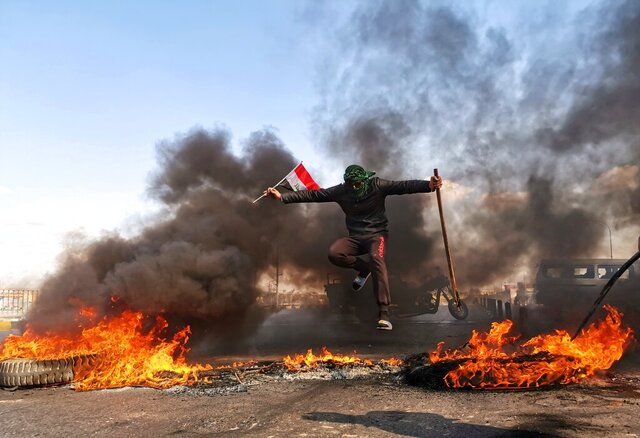 An anti-government protester jumps over burning tires blocking a street during a demonstration against the newly appointed Prime Minister Mohammed Allawi in Najaf, Iraq, Sunday, Feb. 2, 2020. Former communications minister Mohammed Allawi was named prime minister-designate by rival Iraqi factions Saturday after weeks of political deadlock. (AP Photo/Hadi Mizban)