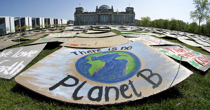 In this Friday, April 24, 2020 file photo, activists place thousands of protest placards in front of the Reichstag building, home of the german federal parliament, Bundestag, during a protest rally of the 'Fridays for Future' movement in Berlin, Germany. World leaders breathed an audible sigh of relief that the United States under President Joe Biden is rejoining the global effort to curb climate change, a cause that his predecessor had shunned. (AP Photo/Michael Sohn, File)