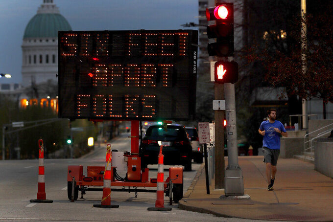 FILE - In this April 2, 2020 file photo, a person jogs past a sign encouraging social distancing, in St. Louis. St. Louis County Executive Sam Page said on Monday, Nov. 9 that unless the surge in COVID-19 cases turns around, the county will be forced to enact new restrictions starting next week. (AP Photo/Jeff Roberson, File)