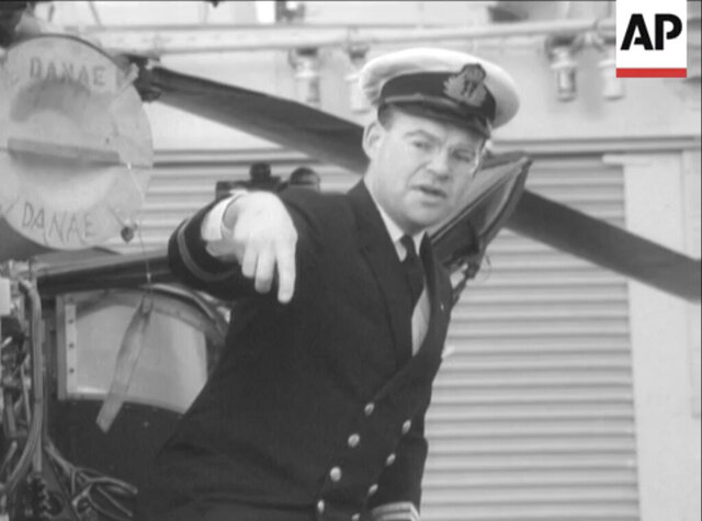 In this image from video taken on Feb. 1, 1971 Lt. Cmdr. Robert Embleton showing schoolchildren around HMS Danae. From resounding applause to ostracization and isolation. That's essentially the journey Lt. Cmdr. Robert Embleton, who served 34 years in Britain's Royal Navy, took by ambulance when discharged from Derriford Hospital in Plymouth, southwest England, on April 8 following his near-month sickness with the coronavirus. (Courtesy of Robert Embleton via AP)