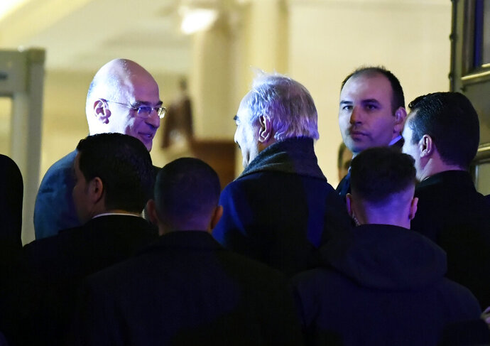 Libyan Gen. Khalifa Hifter, center, shakes hands with the Greek Foreign Minister Nikos Dendias, left, as they surrounded by security in Athens, Thursday, Jan. 16, 2019. Greece will block any European peace deal on Libya unless an agreement between the internationally-recognized government in Tripoli and Turkey on maritime borders is scrapped, Greek Prime Minister Kyriakos Mitsotakis warned Thursday. (AP Photo/Michael Varaklas)