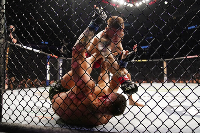 Dustin Poirier, top, punches Conor McGregor during a UFC 264 lightweight mixed martial arts bout Saturday, July 10, 2021, in Las Vegas. (AP Photo/John Locher)
