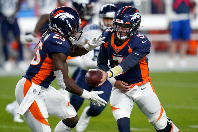 Denver Broncos quarterback Drew Lock (3) hands off to running back Melvin Gordon (25) during the first half of an NFL football game against the Tennessee Titans, Monday, Sept. 14, 2020, in Denver. (AP Photo/Jack Dempsey)