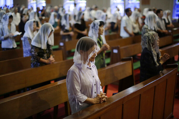 FILE - In this Aug. 9, 2015, file photo, Catholics offer prayers at an early morning Mass to pay respect to the victims of the atomic bombing at the Urakami Cathedral in Nagasaki, southern Japan. The Vatican said Friday, Sept. 13, 2019, Pope Francis will visit Thailand and Japan on Nov. 19-26. (AP Photo/Eugene Hoshiko, File)