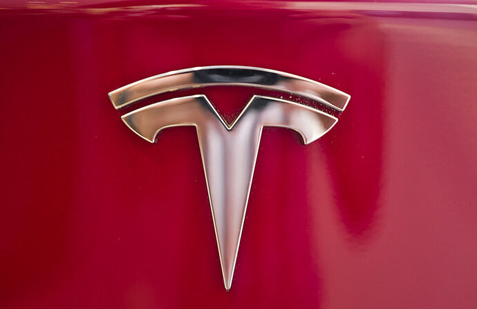 FILE - This Wednesday, Aug. 8, 2018, file photo shows the Tesla emblem on the back end of a Model S in the Tesla showroom in Santa Monica, Calif. Faced with a slumping stock price and questions about demand for its vehicles, Tesla has lowered the U.S. base prices of its two most expensive models. The company on Monday, May 21, 2019 cut $3,000 from the price of the Model S sedan and $2,000 from the Model X SUV.   (AP Photo/Richard Vogel, File)
