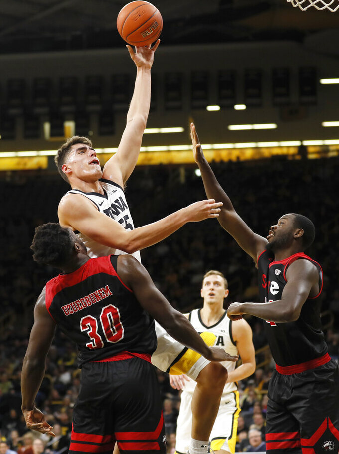 Iowa center Luka Garza shoots over SIU-Edwardsville's Anselm Uzuegbunem (30) and Brandon Jackson, right, during the first half of an NCAA college basketball game, Friday, Nov. 8, 2019, in Iowa City, Iowa.(AP Photo/Charlie Neibergall)