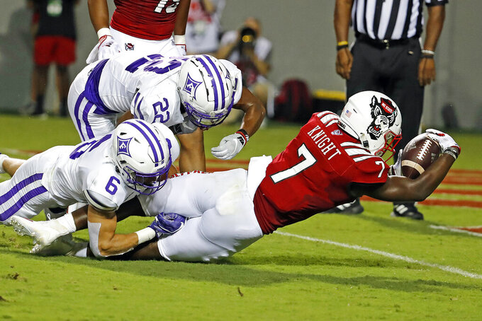North Carolina State's Zonovan Knight (7) stretches for the goal line but falls short while in the grasp of Furman's Hugh Ryan (6) and Ivan Yates (22) during the first half of an NCAA college football game in Raleigh, N.C., Saturday, Sept. 18, 2021. (AP Photo/Karl B DeBlaker)