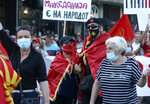 People wearing face masks protest the change of the country's name to North Macedonia and