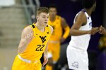 West Virginia guard Sean McNeil celebrates sinking a three-point basket in the second half of an NCAA college basketball game against TCU in Fort Worth, Texas, Tuesday, Feb. 23, 2021. (AP Photo/Tony Gutierrez)