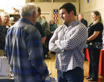 Alek Skarlatos, right, speaks with former Douglas County Commissioner Mike Winters at the Douglas County Republican Party headquarters in Roseburg, Ore., Tuesday,  May 15, 2018. Earlier in the evening Skarlatos announced his intent to run for the Douglas County Commissioner seat recently vacated by Gary Leif. Skarlotos and two friends were traveling in Europe in August 2015 when they incapacitated a heavily armed gunman.  (Michael Sullivan/The News-Review via AP)