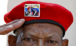 A man wearing the iconic red beret of Venezuela's late President Hugo Chavez, featuring a photo of current President Nicolas Maduro with Chavez, salutes as he waits to enter the Historic Military Museum to visit the leader's remains on the sixth anniversary of his death in Caracas, Venezuela, Tuesday, March 5, 2019. Chavez, who died of cancer, continues to unleash mixed feelings among Venezuelans: some remember him as the father of a revolution that defended the poor, while others blame him for the deep and prolonged crisis that overwhelms the South American country. (AP Photo/Eduardo Verdugo)
