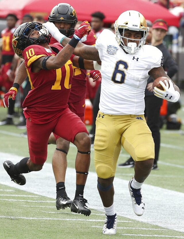 Notre Dame running back Tony Jones Jr. (6) shoves aside Iowa State defensive back Tayvonn Kyle (10) as Jones is on his way to a touchdown during the Camping World Bowl NCAA college football game Saturday, Dec. 28, 2019, in Orlando, Fla. (Stephen M. Dowell/Orlando Sentinel via AP)