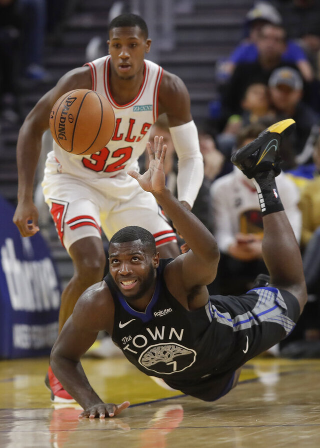 Golden State Warriors forward Eric Paschall (7) dives for the ball in front of Chicago Bulls guard Kris Dunn (32) during the first half of an NBA basketball game in San Francisco, Wednesday, Nov. 27, 2019. (AP Photo/Jeff Chiu)