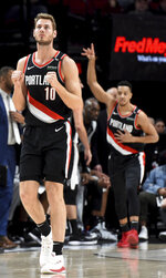 Portland Trail Blazers forward Jake Layman, left, reacts after guard CJ McCollum, right hit a shot at the buzzer to end the first quarter of an NBA basketball game against the San Antonio Spurs in Portland, Ore., Thursday, Feb. 7, 2019. (AP Photo/Steve Dykes)