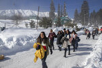 """Indian tourists walk on a snow covered road in Gulmarg, northwest of Srinagar, Indian controlled Kashmir, Monday, Jan. 11, 2021. Snow this winter has brought along with it thousands of locals and tourists to Indian-controlled Kashmir's high plateau, pastoral Gulmarg, which translates as """"meadow of flowers."""