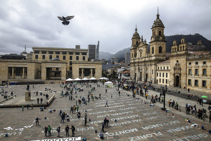 """FILE - This June 10, 2019 file photo shows activists who have received death threats displaying the names of killed leftist activists as part of an art installation by Colombia artist Doris Salcedo at Plaza Bolivar in downtown Bogota, Colombia.  The United Nations High Commissioner for Human Rights expressed alarm Tuesday, Jan. 14, 2020 at the """"staggering number"""" of social activists killed in Colombia despite a peace accord aimed at improving conditions in poor, rural areas. (AP Photo/Ivan Valencia, File)"""