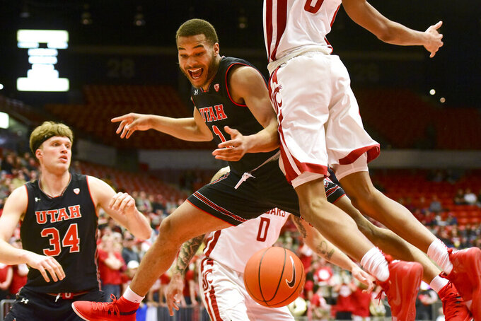Utah guard Charles Jones Jr (1) loses control of the ball after driving to the basket as Washington State forward Marvin Cannon (5) defends during the first half of an NCAA college basketball game Saturday, Feb. 23, 2019, in Pullman, Wash. (Pete Caster/Lewiston Tribune via AP)