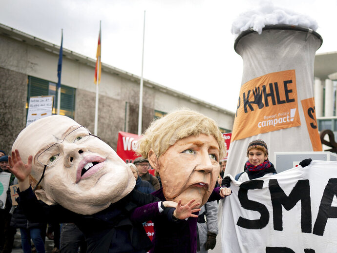 Activists depicting German Chancellor Angela Merkel, right, and German Economy Minister Peter Altmaier are protesting in front of the Federal Chancellery against the coal phase-out law and the resulting delayed coal phase-out in Berlin, Germany, Wednesday, Jan.29, 2020. (Kay Nietfeld/dpa via AP)