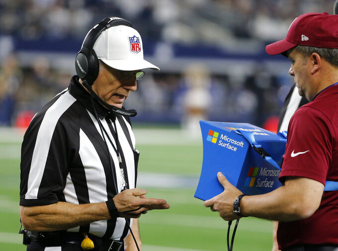 "FILE  - In this Jan. 5, 2019, file photo, referee Walt Anderson (66) watches a replay on a Microsoft Surface during an NFC wild-card NFL football game between the Seattle Seahawks and Dallas Cowboys, in Arlington, Texas. The NFL's competition committee discussed the league's replay system during its annual meeting in Indianapolis but reached no consensus on possible changes. And it may not recommend any major alterations. New York Giants owner John Mara told a handful of reporters Tuesday, Feb. 26, 2019, that he didn't sense a ""lot of support"" among committee members to expand reviewable calls. (AP Photo/Michael Ainsworth, File)"