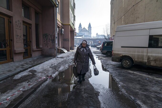 A woman walks through an empty street in Ivano-Frankivsk, western Ukraine, Thursday, Feb. 25, 2021. Ukraine has recorded a 50% increase in the number of daily new coronavirusinfections, as the country takes the first steps in its vaccination campaign. Health Minister Maxim Stepanov said Thursday that 8,417 new infections were found over the past day, up from 5,424 a day earlier. (AP Photo/Evgeniy Maloletka)