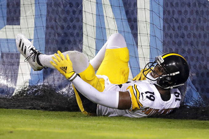 Pittsburgh Steelers wide receiver JuJu Smith-Schuster slides into the padding on the stands after catching a 17-yard touchdown pass against the Tennessee Titans in the first half of a preseason NFL football game Sunday, Aug. 25, 2019, in Nashville, Tenn. (AP Photo/Mark Zaleski)