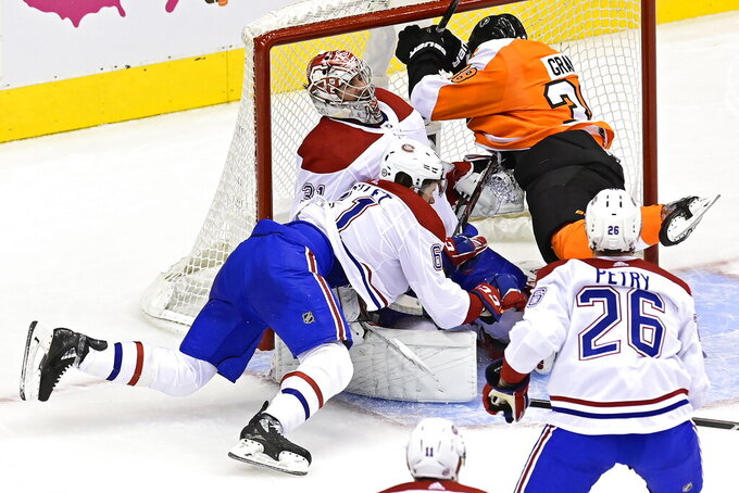 Philadelphia Flyers' Derek Grant (38) and Montreal Canadiens' Xavier Ouellet (61) crash into Canadiens goaltender Carey Price (31) during the first period of an NHL Eastern Conference Stanley Cup hockey playoff game in Toronto, Wednesday, Aug. 12, 2020. (Frank Gunn/The Canadian Press via AP)