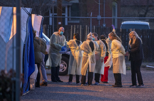 Medical personnel prepare to test patients at a mobile site for coronavirus testing across the street from Lovelace Hospital on Friday, March 13, 2020, in Albuquerque, N.M. (Roberto E. Rosales/The Albuquerque Journal via AP)