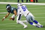 Philadelphia Eagles quarterback Jalen Hurts (2) fumbles the ball as he's sacked by Dallas Cowboys defensive end Randy Gregory (94) in the second half of an NFL football game in Arlington, Texas, Sunday, Dec. 27. 2020. The Eagles recovered the fumble. (AP Photo/Michael Ainsworth)
