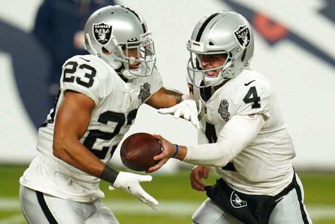 Las Vegas Raiders quarterback Derek Carr (4) hands the ball to running back Devontae Booker (23) during the second half of an NFL football game against the Denver Broncos, Sunday, Jan. 3, 2021, in Denver. (AP Photo/Jack Dempsey)