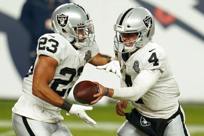 Las Vegas Raiders quarterback Derek Carr (4) hands the ball to running back Devontae Booker (23) during the second half of an NFL football game against the Denver Broncos, Sunday, Jan. 3, 2021, in Denver. (AP Photo/Jack Dempsey)