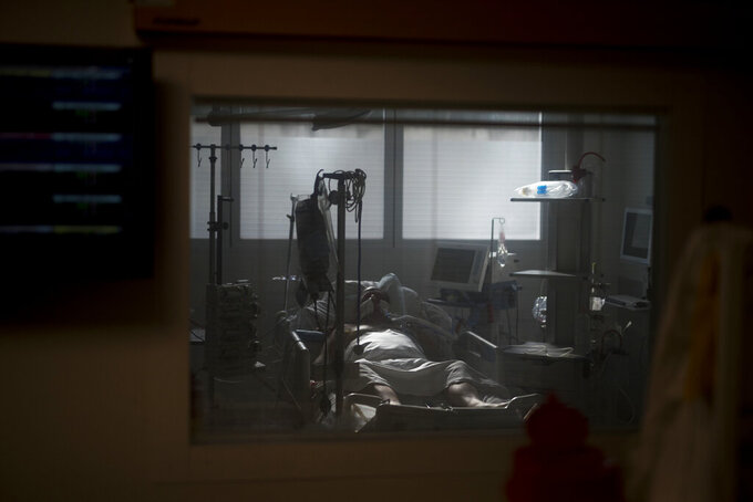 A 60-year-old COVID-19 patient is pictured through the window of an ICU room at the La Timone hospital in Marseille, southern France, Thursday, Nov. 12, 2020. (AP Photo/Daniel Cole)
