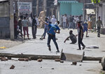 A Kashmiri protester throws stones on government forces as they attempt to march on the streets in solidarity with rebels engaged in a gunbattle with soldiers, in Srinagar, Indian controlled Kashmir, Thursday, Sept. 17, 2020. The gunfight erupted shortly after scores of counterinsurgency police and soldiers launched an operation based on a tip about the presence of militants in a Srinagar neighborhood, Pankaj Singh, an Indian paramilitary spokesman, said. (AP Photo/Mukhtar Khan)