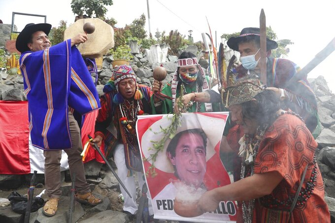 Shamans hold a photo of presidential candidate Pedro Castillo of the Free Peru party, as they perform a good luck ritual ahead of the presidential runoff election, at the Cerro San Cristobal in Lima, Peru, Wednesday, May 26, 2021. The June 6 runoff pits Castillo against Keiko Fujimori, the daughter of former President Alberto Fujimori. (AP Photo/Martin Mejia)