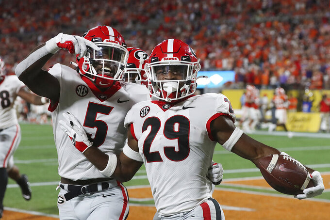 Georgia defensive back Christopher Smith celebrates with Kelee Ringo, left, after intercepting a Clemson pass and returning it for a touchdown during the second quarter of an NCAA college football game Saturday, Sept. 4, 2021, in Charlotte, N.C. (Curtis Compton/Atlanta Journal-Constitution via AP)