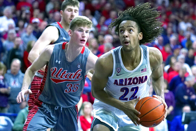 Arizona forward Zeke Nnaji (22) drives past Utah center Branden Carlson during the second half of an NCAA college basketball game Thursday, Jan. 16, 2020, in Tucson, Ariz. Arizona won 93-77. (AP Photo/Rick Scuteri)