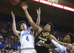 Colorado's forward Evan Battey, center, and UCLA's guard Jaime Jaquez Jr. (4) and guard David Singleton compete for a rebound during the first half of an NCAA college basketball game Thursday, Jan. 30, 2020, in Los Angeles. (AP Photo/Michael Owen Baker)