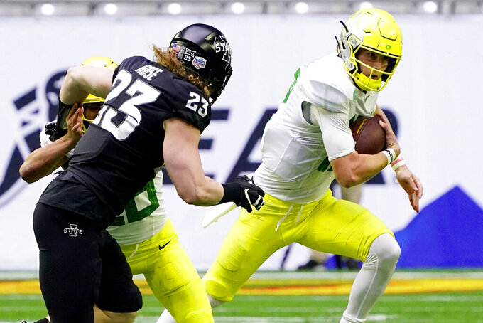 Oregon quarterback Tyler Shough scrambles as Iowa State linebacker Mike Rose (23) pursues during the first half of the Fiesta Bowl NCAA college football game, Saturday, Jan. 2, 2021, in Glendale, Ariz. (AP Photo/Rick Scuteri)
