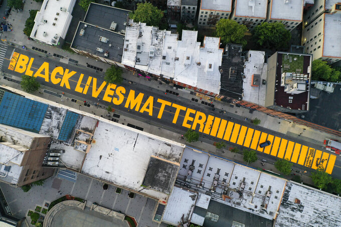"""FILE - In this June 15, 2020, file photo, a giant """"Black Lives Matter"""" sign is painted on Fulton Street in the Brooklyn borough of New York. A report released on Wednesday, Aug. 25, 2021 says 16% of American households donated to racial and social justice causes in 2020, resulting in a 3% uptick from 2019 as donors raced to provide support to affected communities in a year marked by protests and increased attention on racism in America. (AP Photo/John Minchillo, File)"""